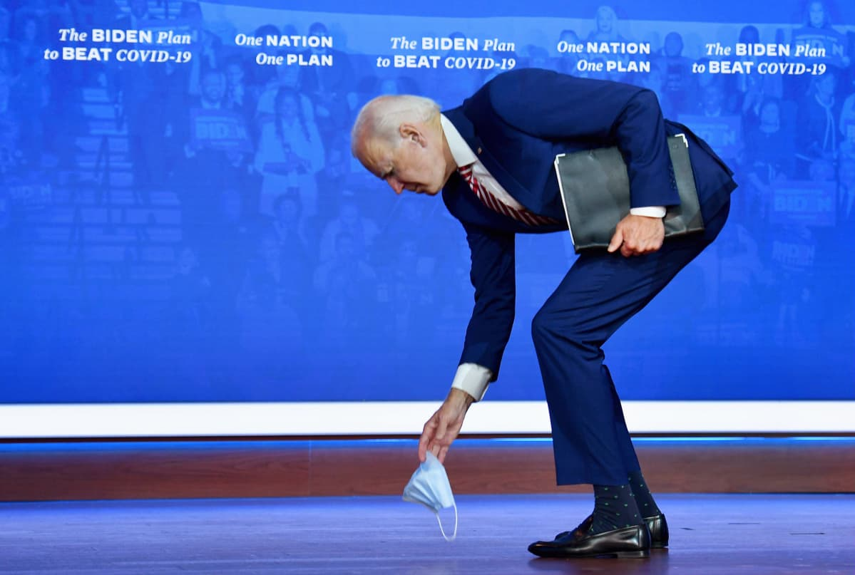 Joe Biden nostaa vaalitilaisuudessa lavalle pudonneen kasvomaskinsa.