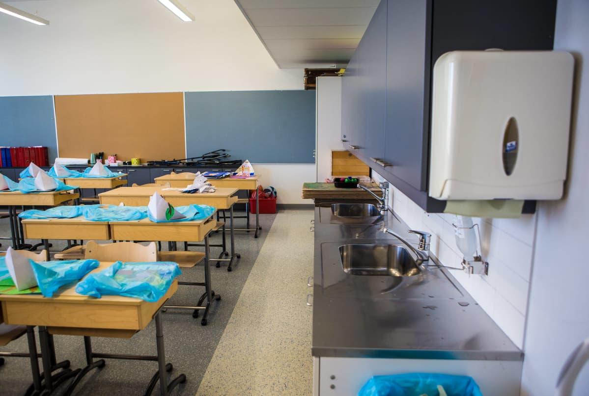 Luokkahuone ja käsienpesupiste Naistenmatkan koulussa.