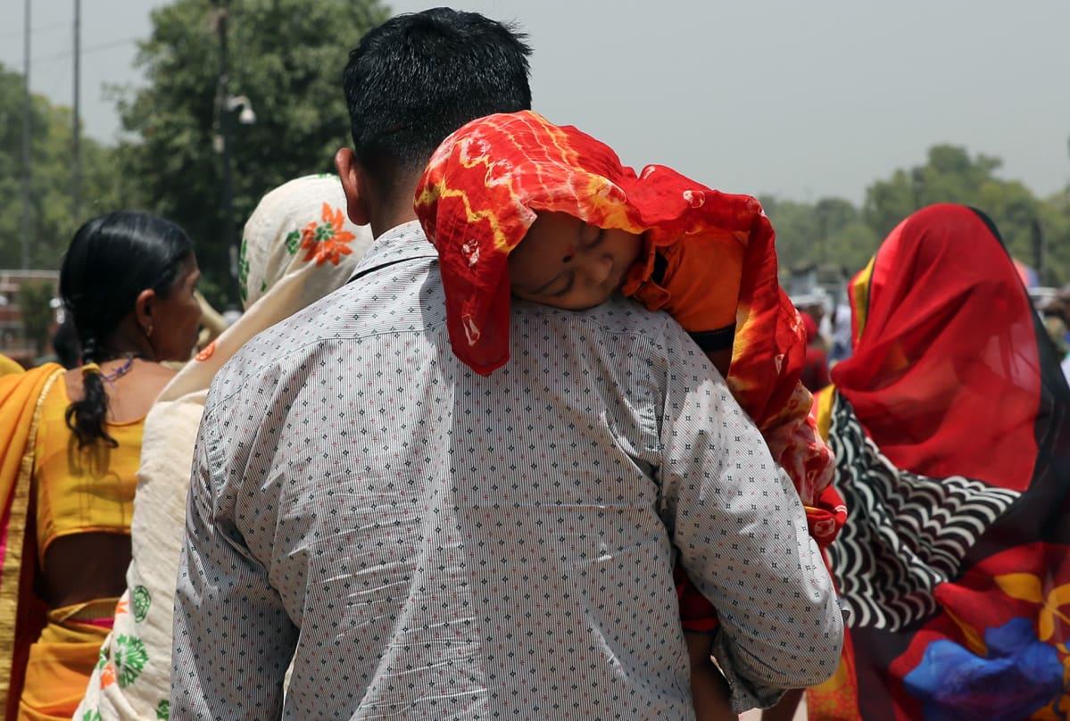 Intialainen mies suojasi vauvaa liinalla kesäkuun helteissä Delhissä.