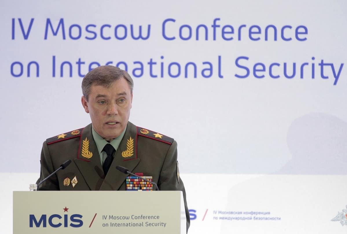 Kenraali Gerasimov seisoo puhujankorokkeen takana Moskovassa kansainvälisen turvallisuuden konferenssissa. Hänellä on yllään vihreä univormu, rintamuksessaan rivi kunniamerkkejä ja lehväkuviot kauluksissa.