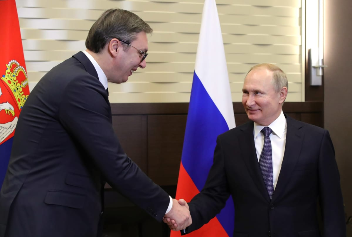 Aleksandar Vucic ja Vladimir Putin kättelevät maidensa lippujen edessä