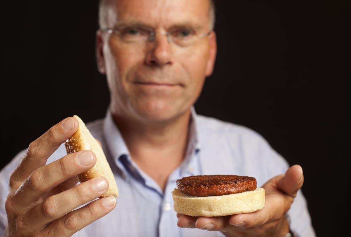 Professori pitää kädessään laboratoriossa kasvatetusta lihasta tehtyä hampurilaista