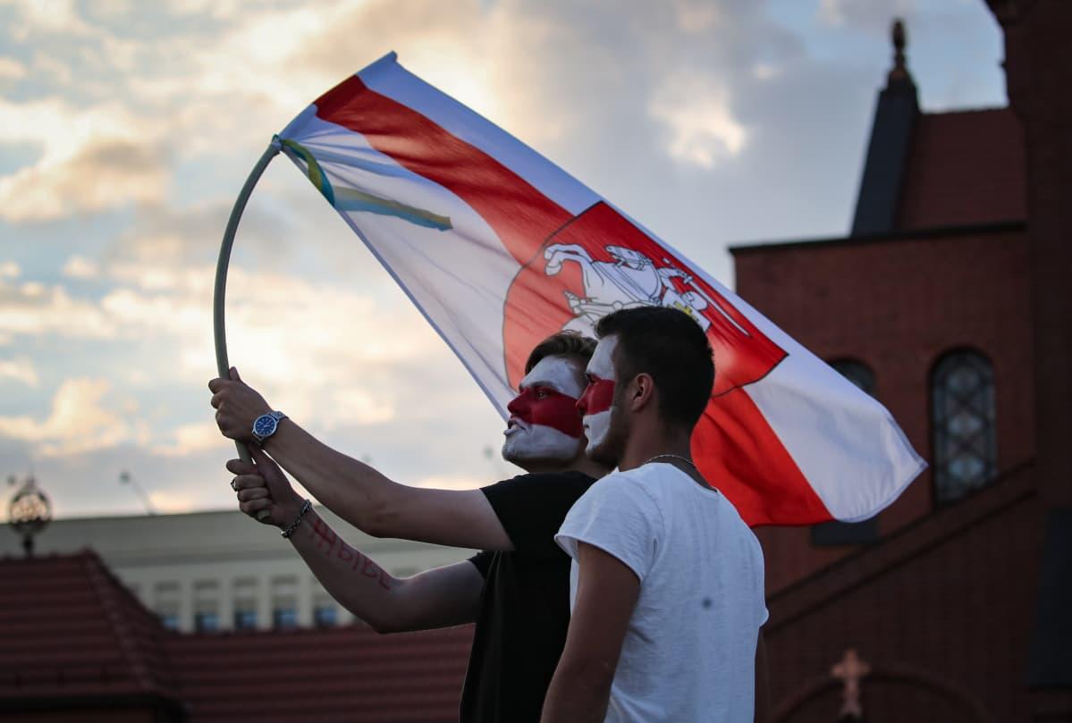 Mielenosoittajat punavalkoisen lipun kanssa