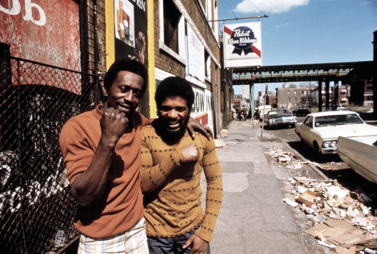 Kaksi nuorta mustaa miestä seisoo rapistuneen näköisellä kadulla. Toinen näyttää hymyillen nyrkkiään, toinen nauraa. Kadun varteen on parkkeerattu leveitä 70-luvun autoja.