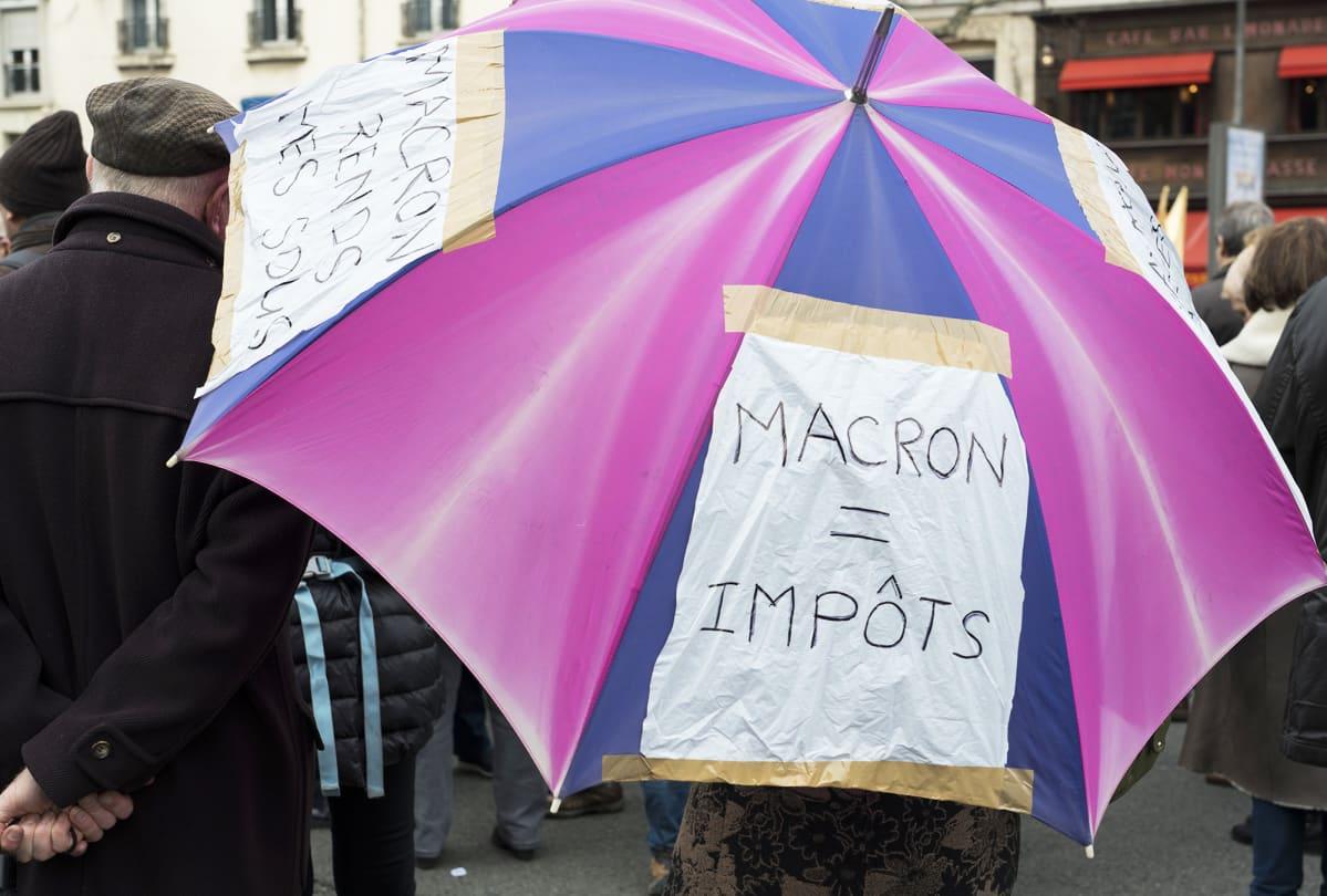 Macron on yhtä kuin verot, luki mielenosoittajan sateenvarjossa.