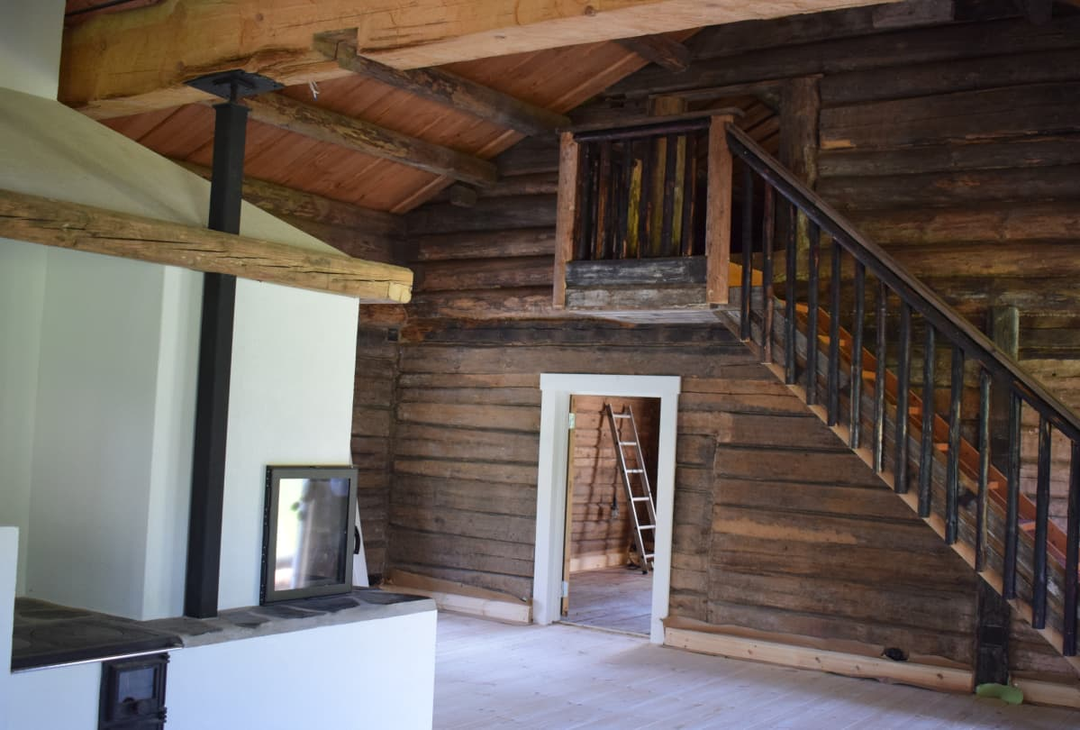Uuden talon sisusta alkaa muotoutua. Ikivanhat hirret ja lankut saavat rinnalleen modernin tulisijan.