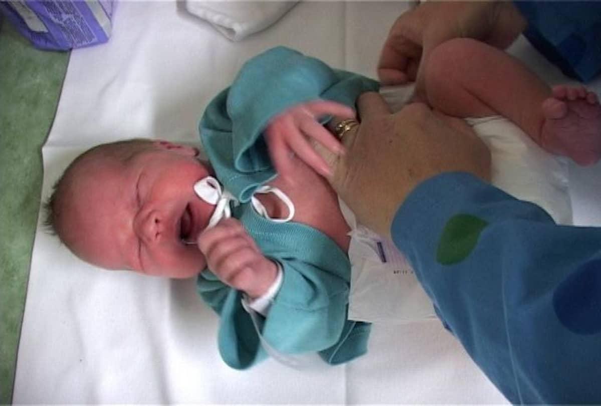 Vastasyntynyt vauva sairaalan vaatteissa.