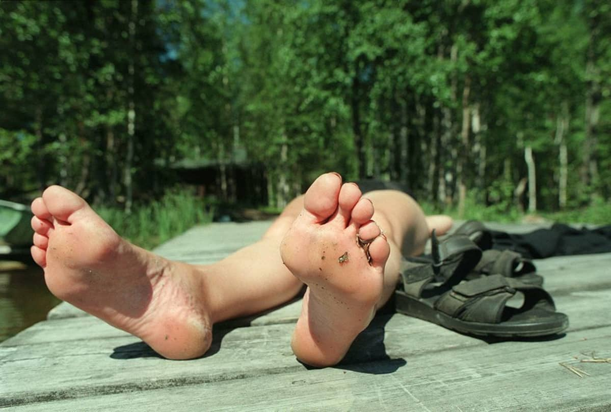 Paljaat jalat laiturilla.