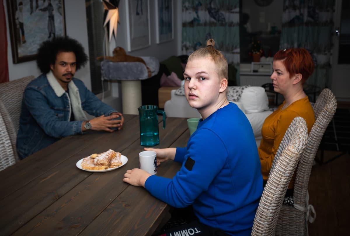 Jasper ja Tiina Mäki-Jokela istuvat kahvipöydän ääressä Perjantain juontajan Sean Ricksin kanssa.