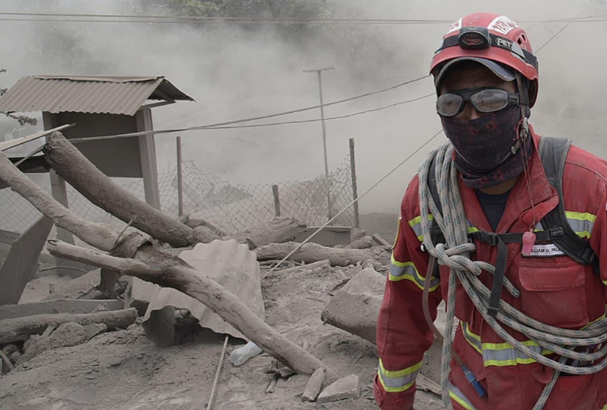 Guatemalalainen pelastustyöntekijä auttamassa tulivuorenpurkauksen uhreja.
