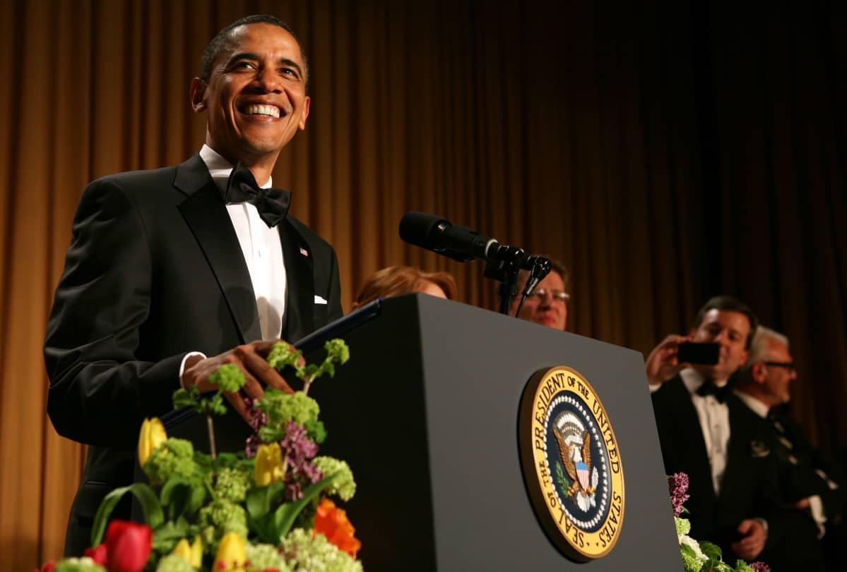 Presidentti Barack Obama puhuu Valkoisen talon kirjeenvaihtajayhdistyksen gaalaillallisilla. Obama hymyilee leveästi.