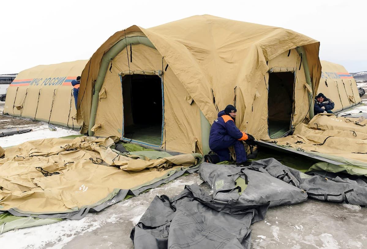 Mies istuu siirrettävän telttasairaalan edustalla Muurmanskissa.
