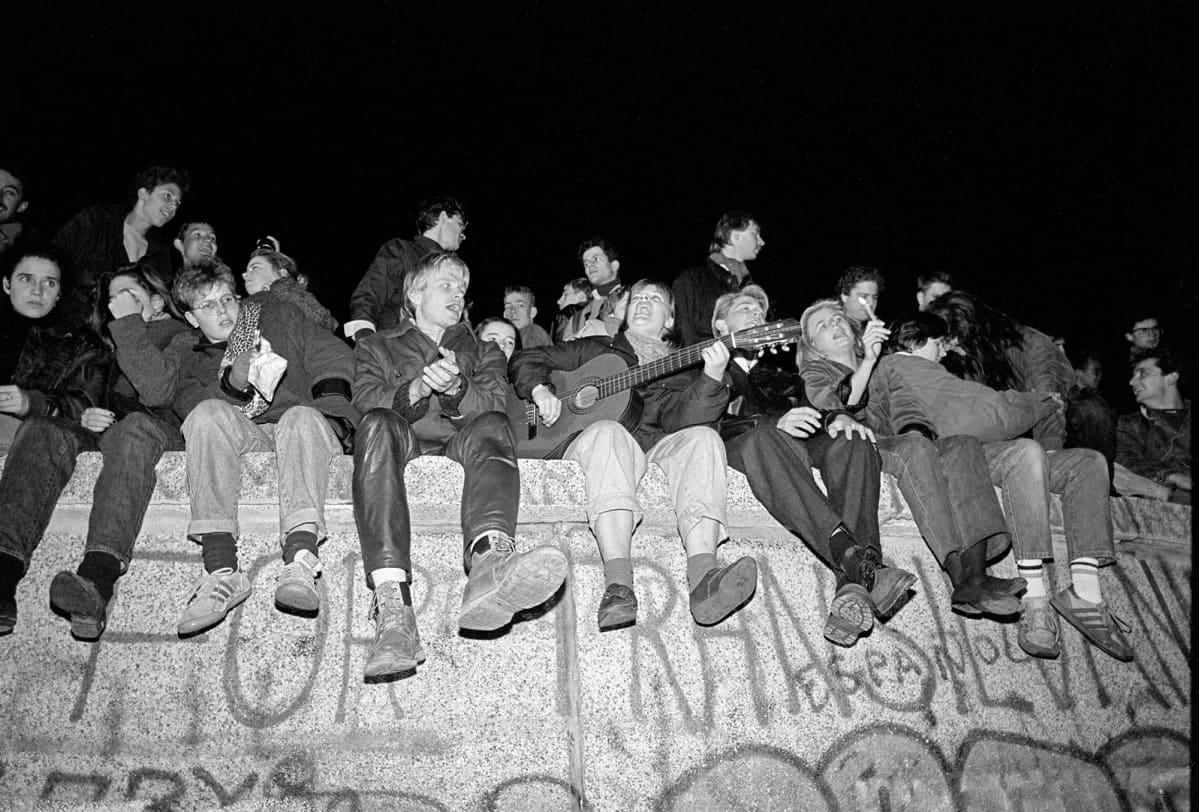 Kuvassa nuori istuu murtuneella Berliinin muurilla.