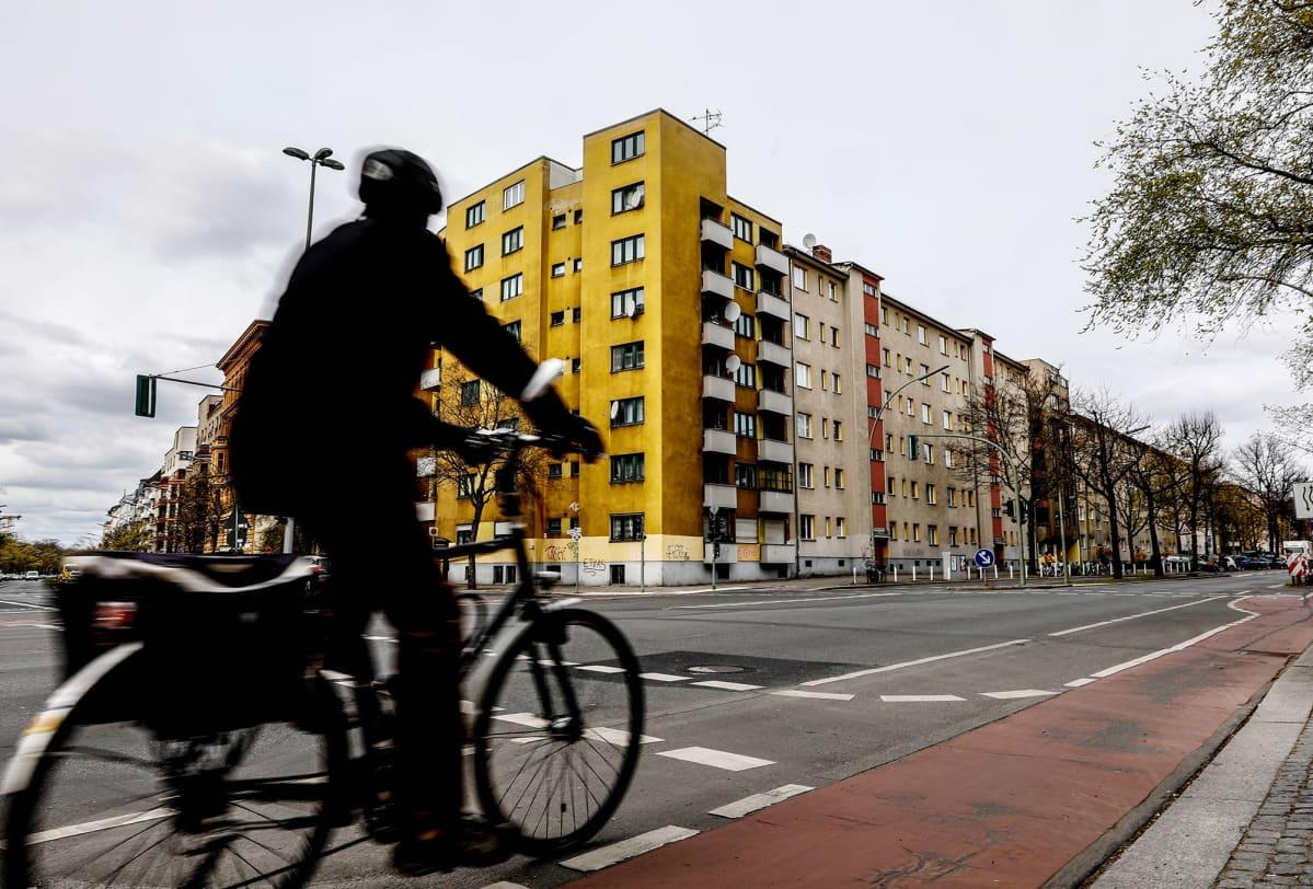 Pyöräilijä ohittaa risteyksen ja taustalla asuinrakennuksia Berliinissä.