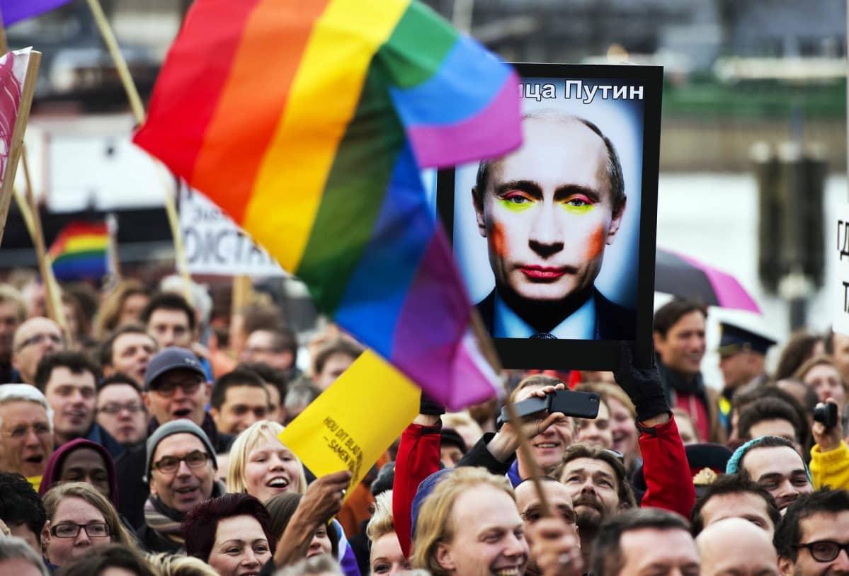 Mielenosoituksessa heilutetaan sateenkaarilipuja ja kannetaan kuvaa, joka esittää vahvasti meikatun Putinin.
