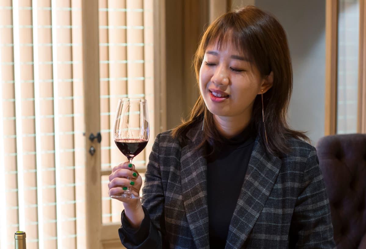 Nainen viinilasi kädessään.