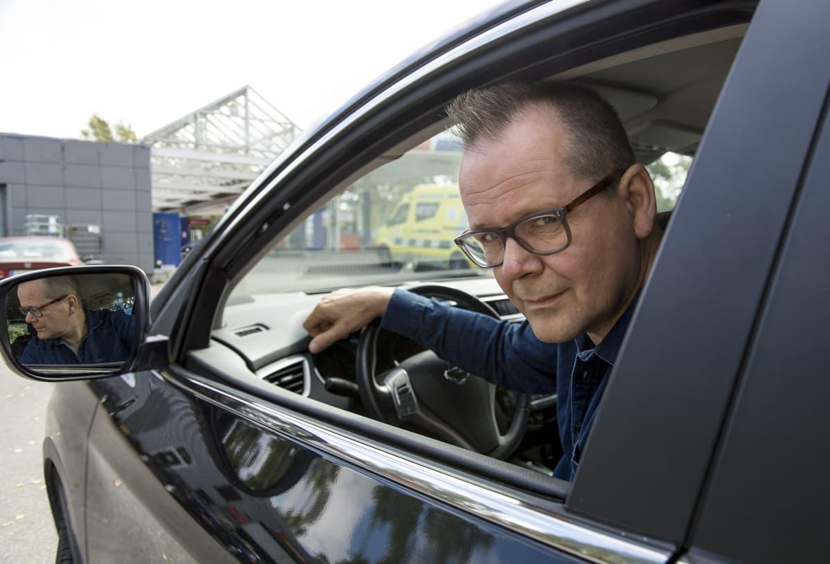 Kari Hotakainen istuu autossa.