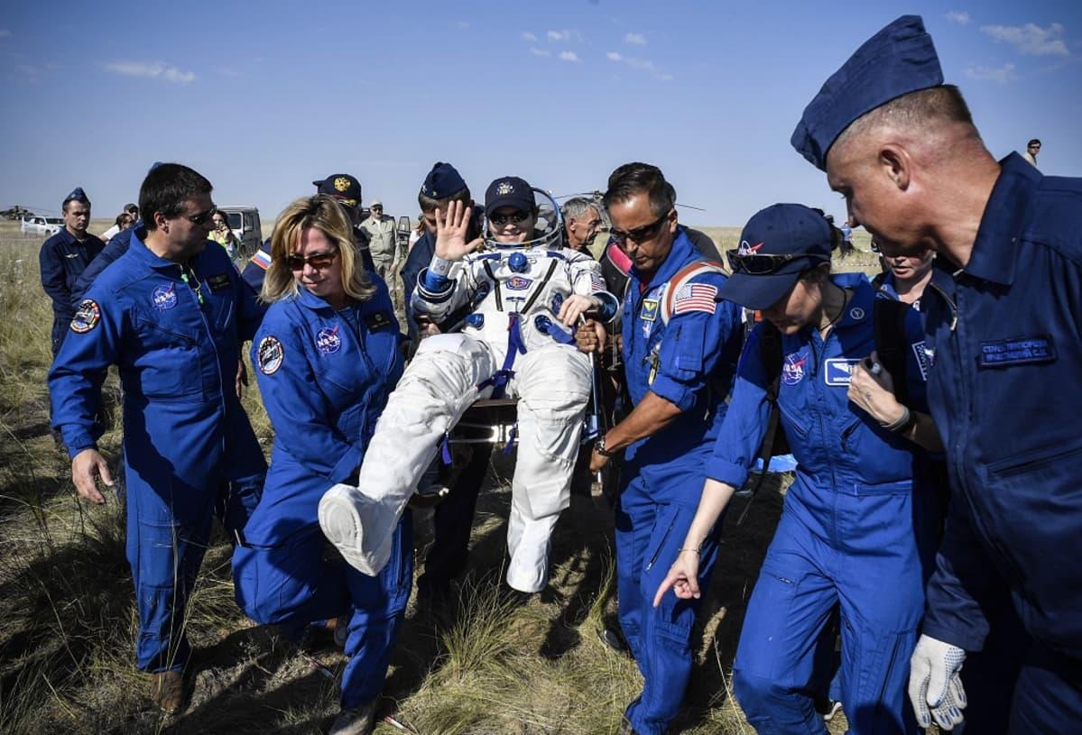 Nasan työntekijät kantavat vilkuttavan astronautin istuintia.