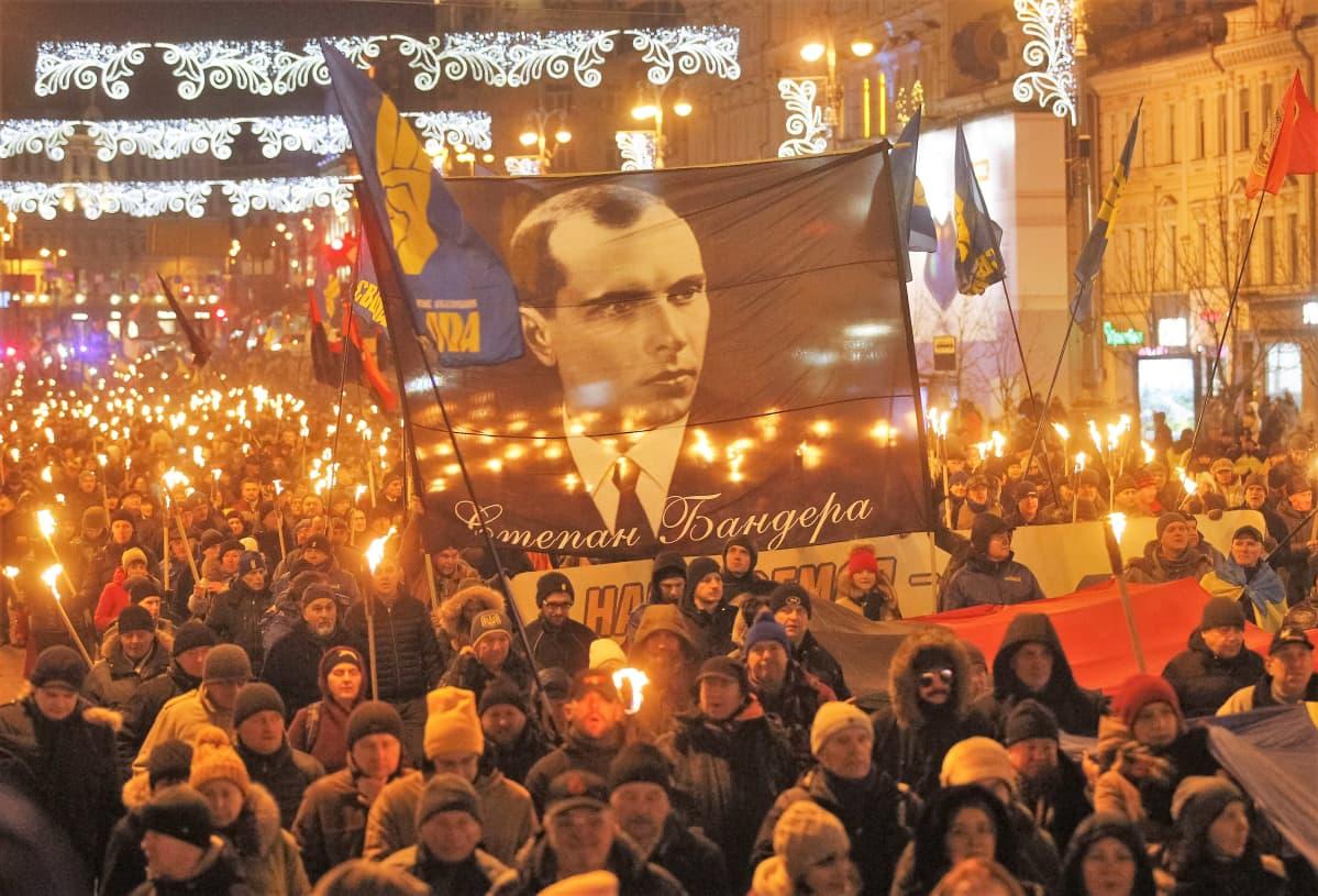 Soihtukulkue marssii kadulla. Marssijoilla on suuri plakaatti, jossa on Stepan Banderan kuva.