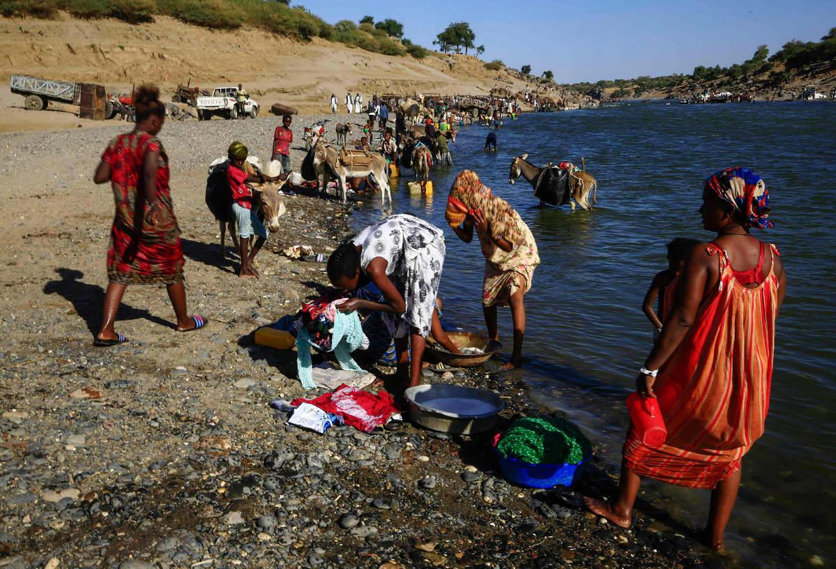 Pakolaiset peseytyvät joessa.