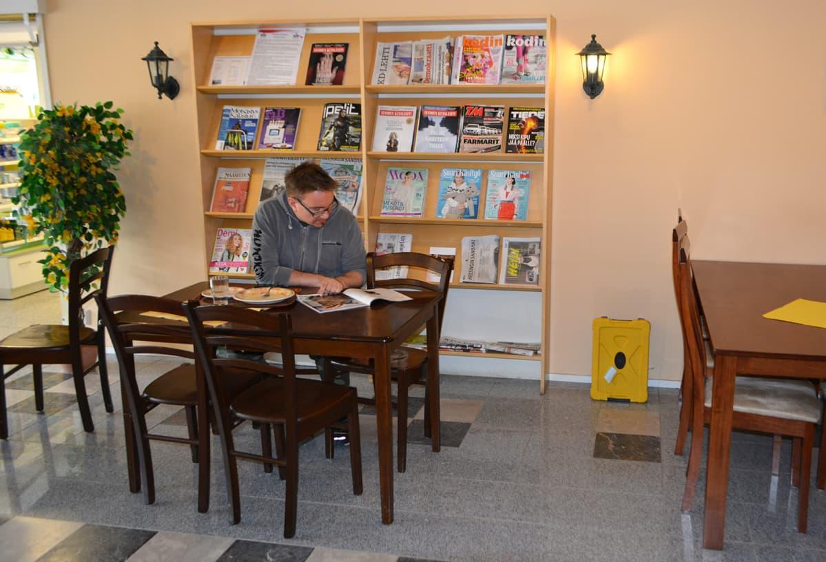Mies lukee pöydässä lehteä.