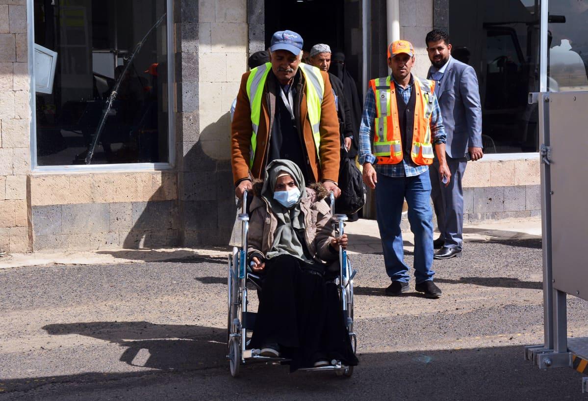 Sairasta jemeniläistä saatetaan pyörätuolissa lentokoneeseen Sanaassa.