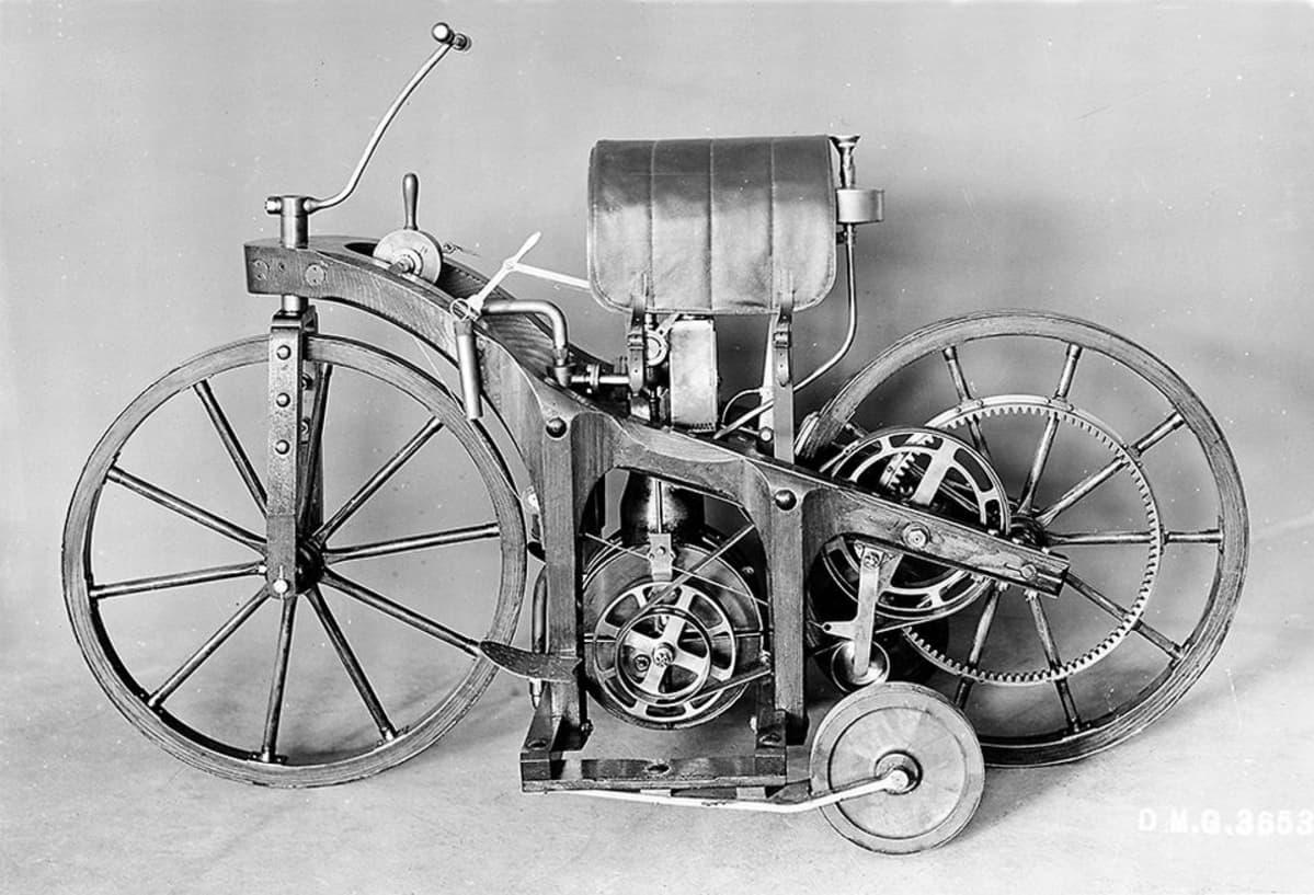 Kuvan polkupyörän ja moottoripyörän hybridistä, jossa on myös satula ja apupyörät.