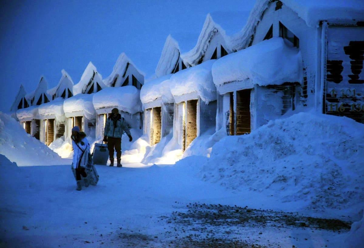 Turisteja lumisessa maisemassa Saariselällä.