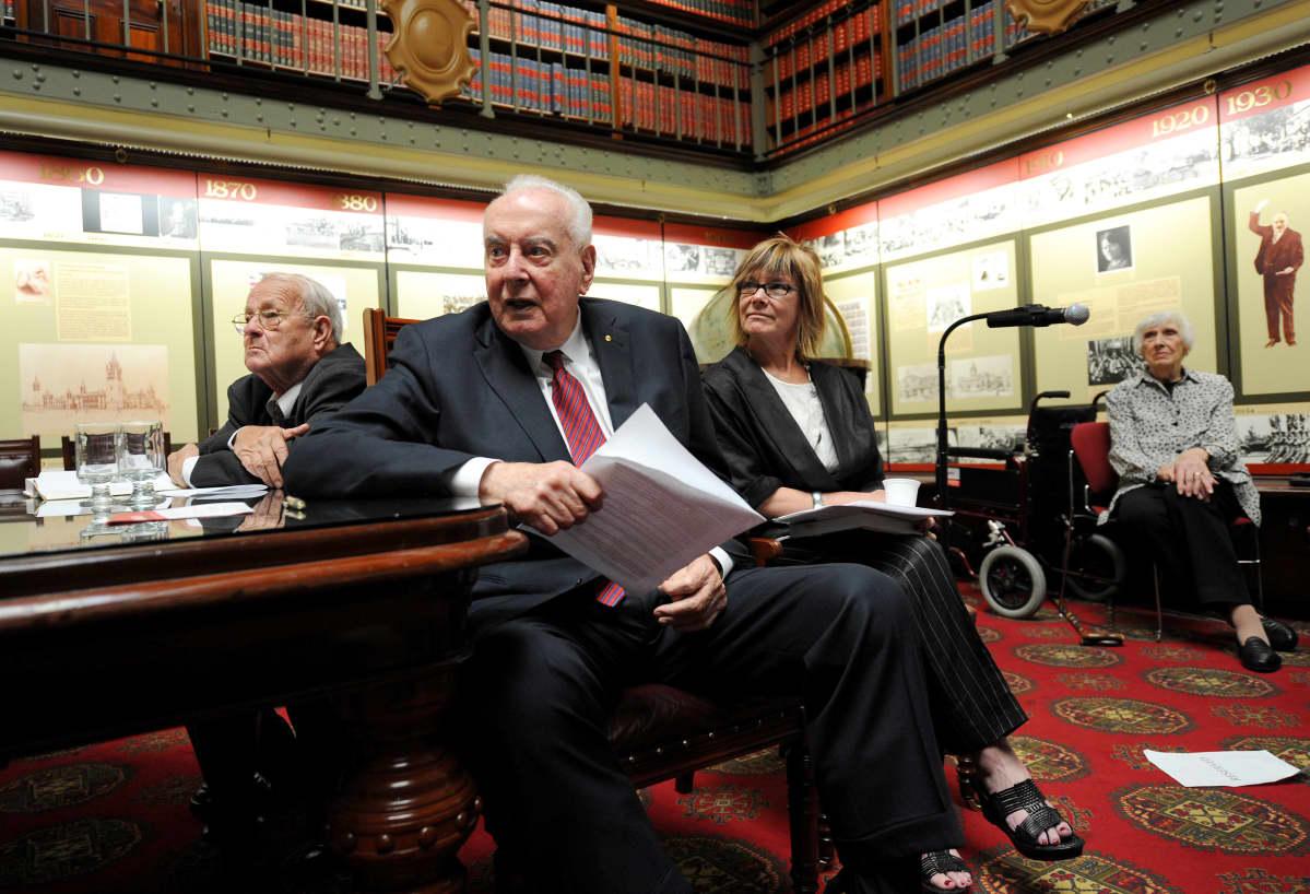 Neljä ihmistä istuu kirjastossa, etualalla papereita pitelevä Gough Whitlam