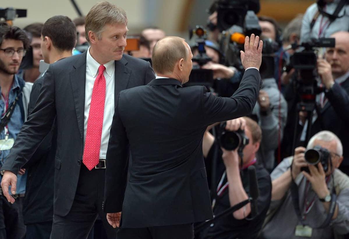 Vladimir Putin ja hänen tiedottajansa Dmitri Peskov (vas.) Putinin jokavuotisen suora linja -ohjelman jälkeen Moskovassa 16. huhtikuuta.