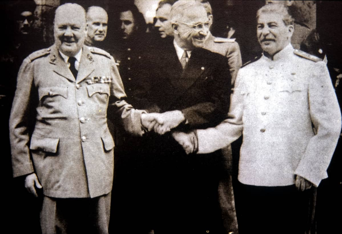 Winston Churchill, Harry S. Truman ja Josef Stalin pitävät toistensa käsistä kiinni. Churchillillä ja Stalinilla on univormut, Trumanilla tumma puku.