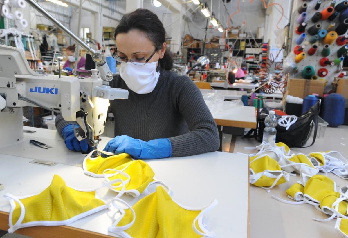 Koronavirus ajaa tehtaita konkurssiin, mutta italialaisella, hengityssuojia valmistavalla tehtaalla Besozzossa riitti töitä.