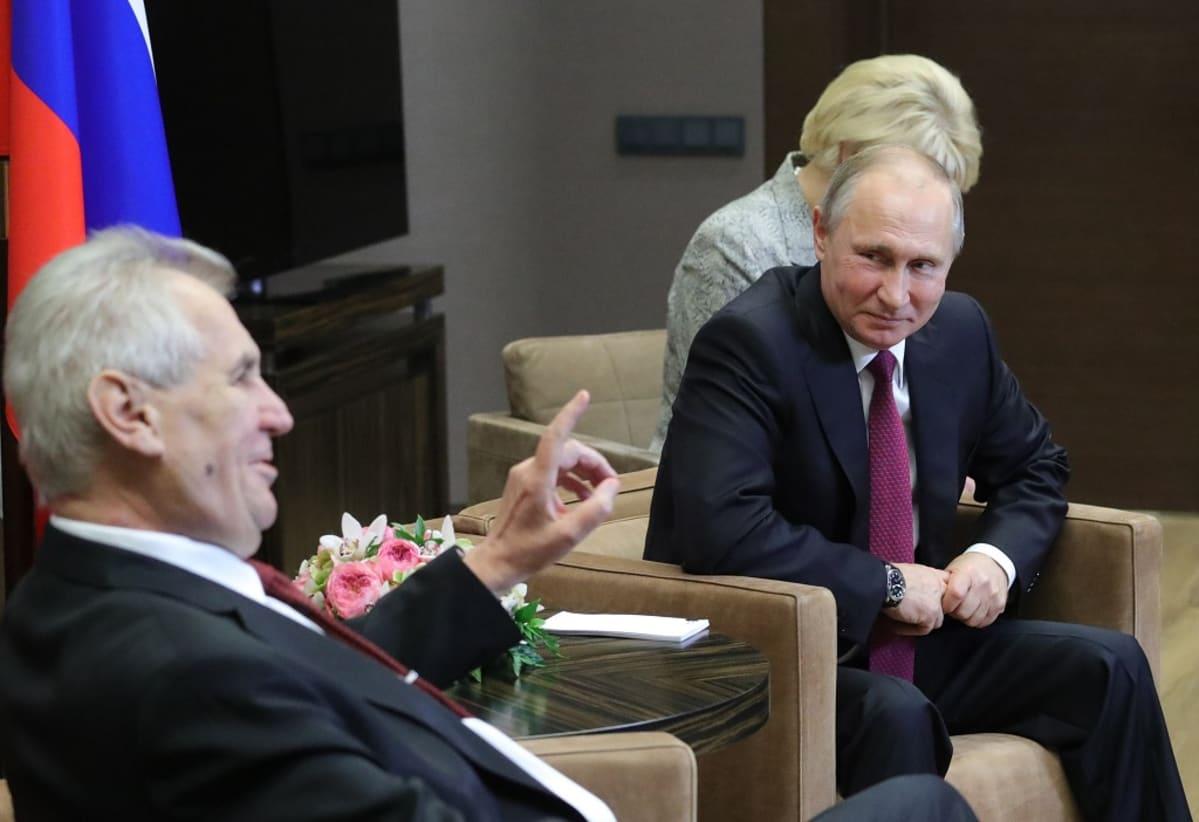 Zeman ja Putin istuvat nojatuoleissa, Zeman puhuu, Putin hymyilee.  Taustalla näkyy Venäjän lippu ja Putinin takana istuu nainen, mahdollisesti tulkki.