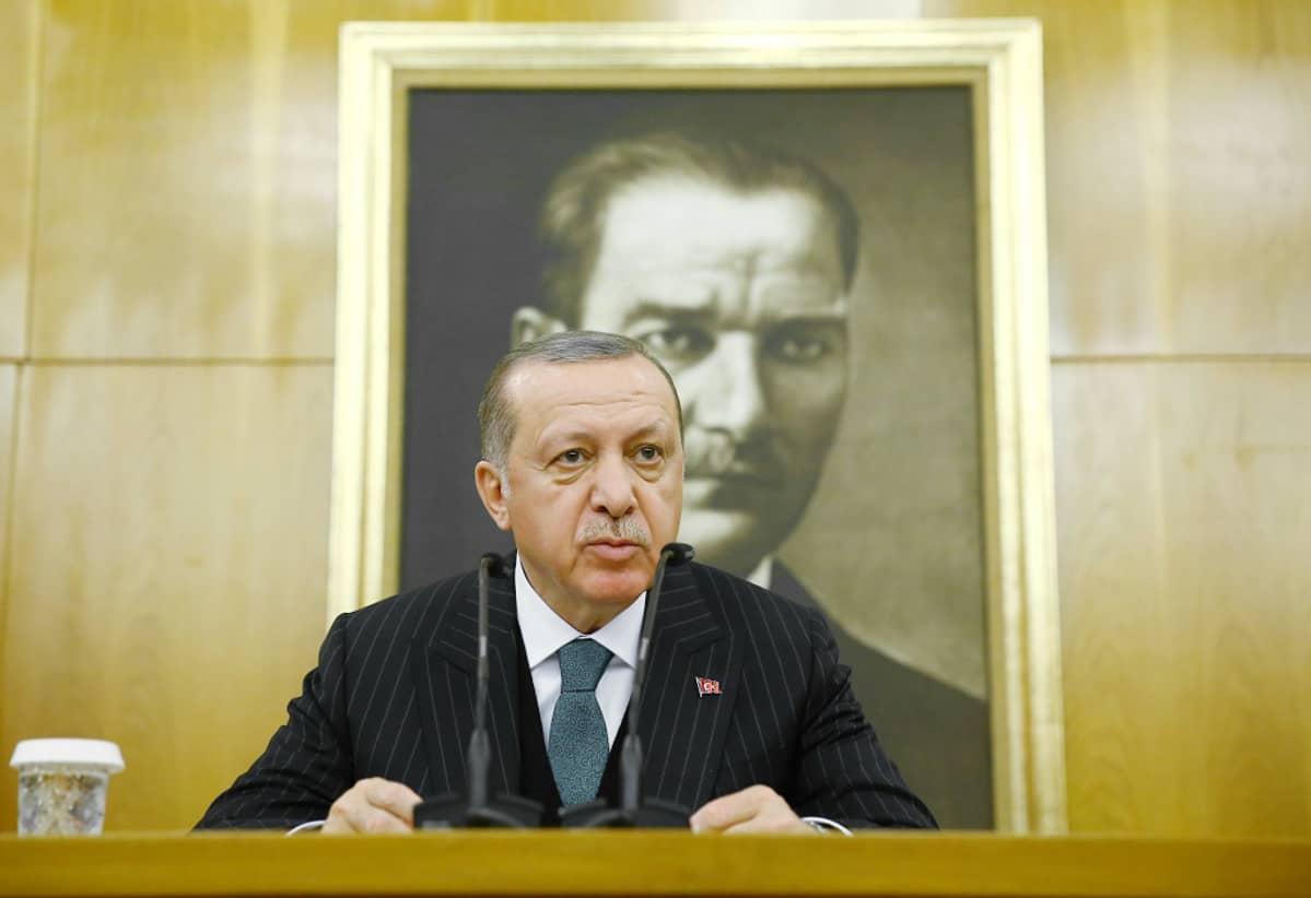 Erdoğan puhuu pöydän takana mikrofoneihin. Takana näkyy Turkin presidentin Mustafa Kemal Atatürkin muotokuva.