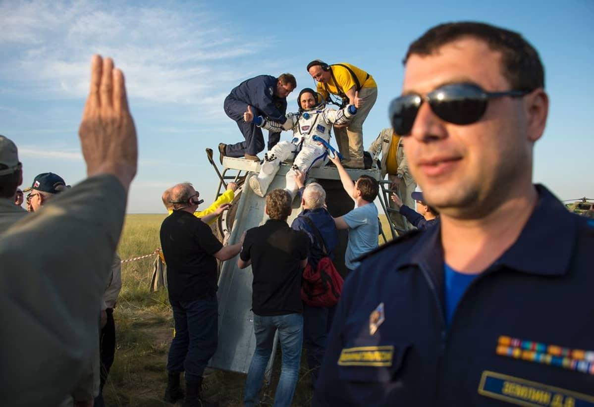 Ihmiset tervehtivät juhlien avaruudesta takaisin maan päälle saapuneita astronautteja.