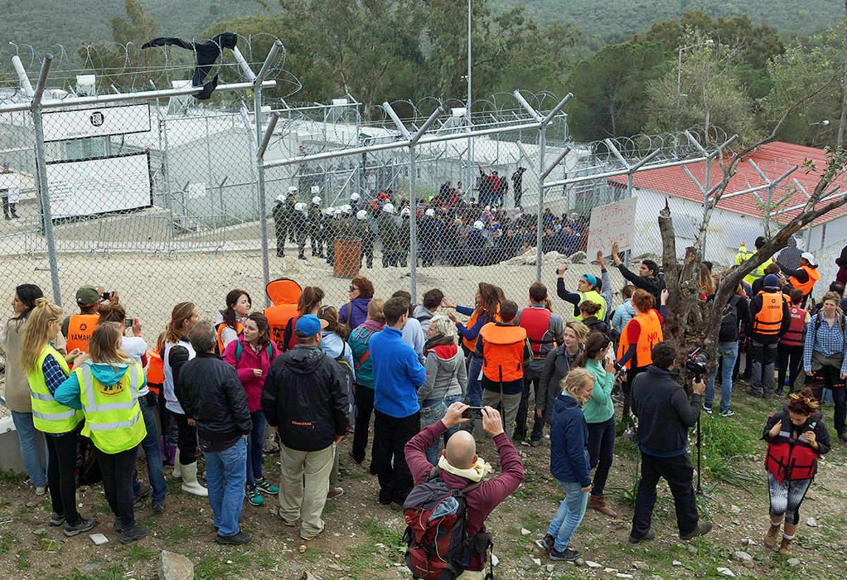 Ihmisiä pakolaisleirin ulkopuolella.