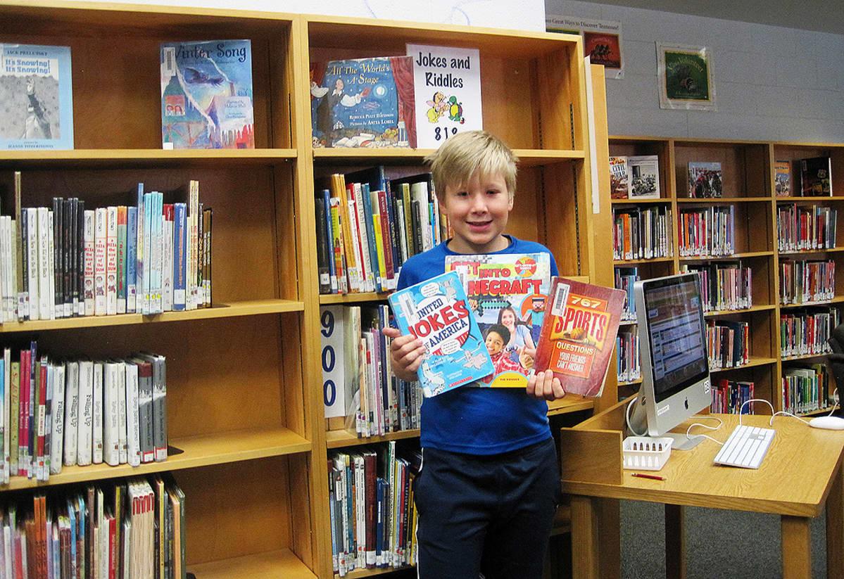 Kuvassa poika esittelee kirjoja.