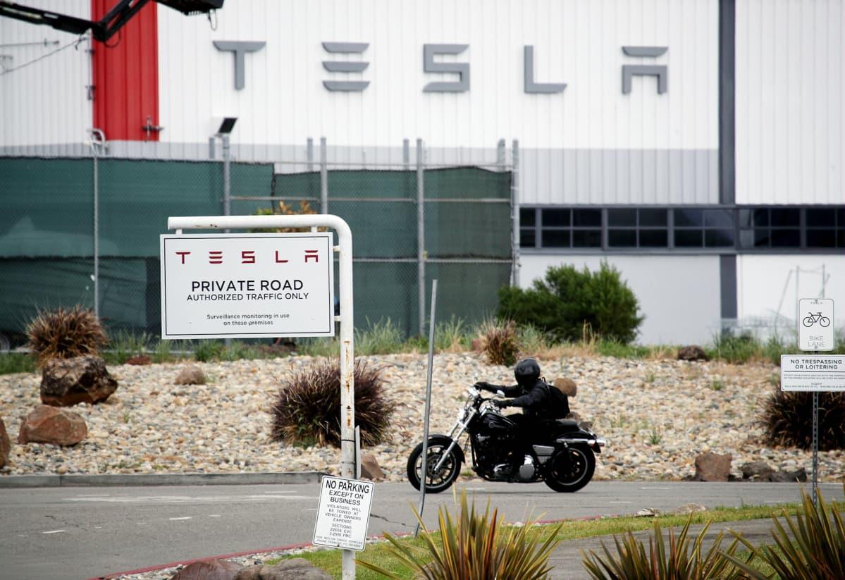 Moottoripyöräilijä Teslan tehtaan edustalla Kaliforniassa.