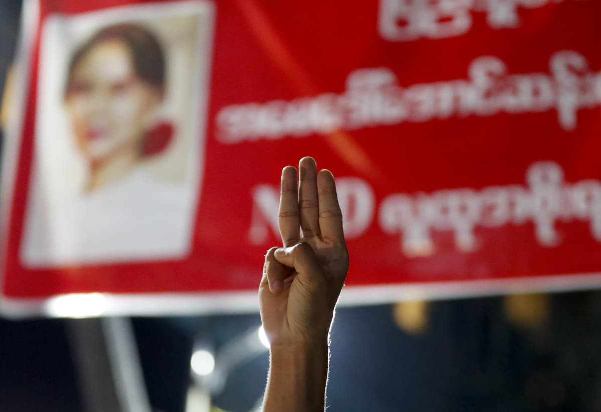 Yangonissa mielenosoittaja kohotti kolme sormea armeijan syrjäyttämän Aung San Suu Kyin kuvalle. Kyseessä on vastarinnan symboli.