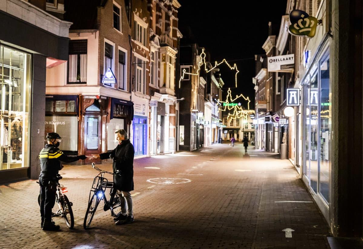 Polkupyöräilevä poliisi tarkastaa toisen polkupyöräilijän papereita autiolla kävelykadulla pimeän aikaan.