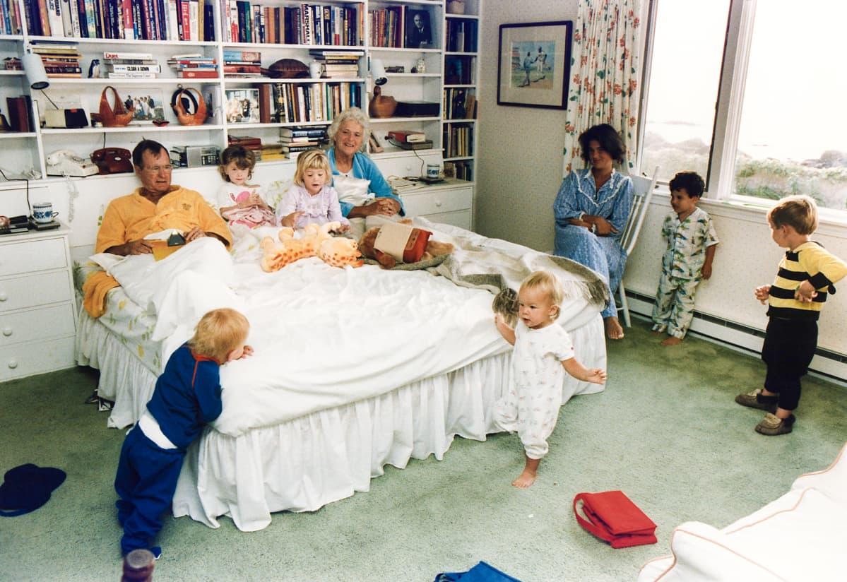 Bushit vuoteessa ja lapsenlapsia ympärillä