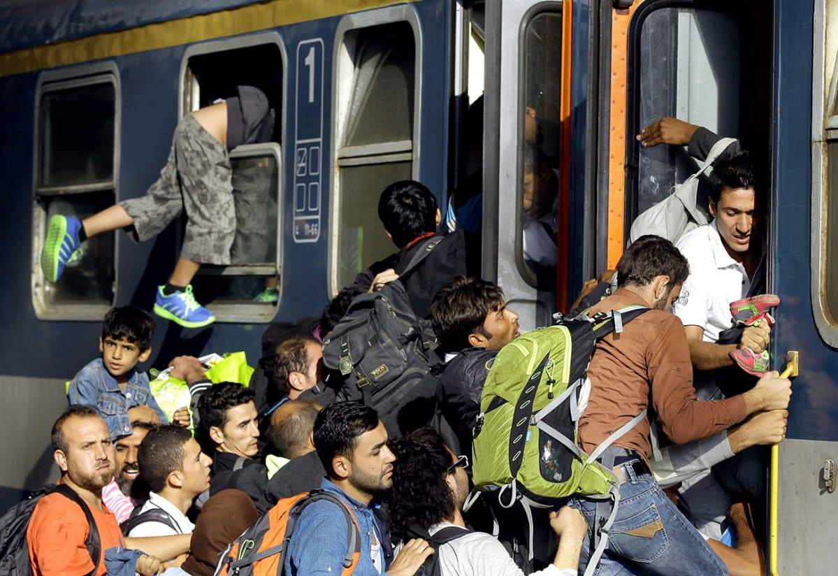 Turvapaikanhakijoita nousemassa junaan Budapestin päärautatieasemalla.