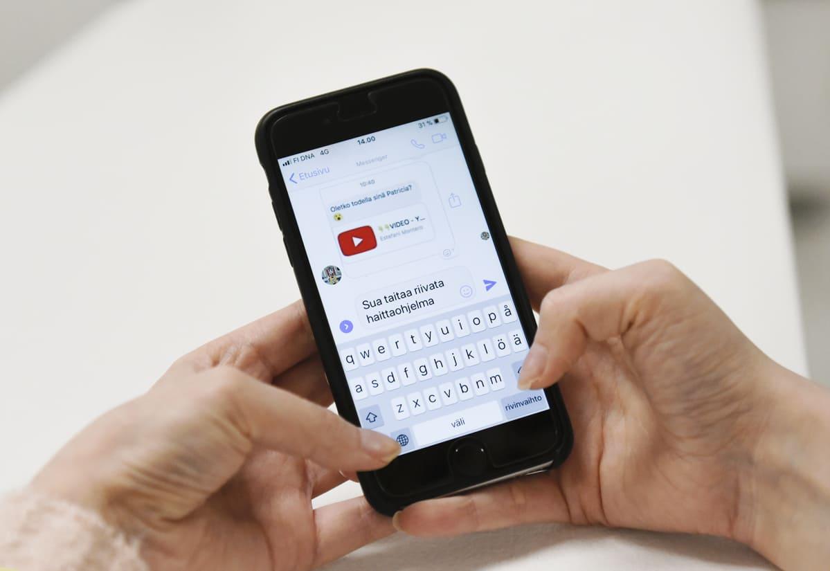 Nainen puhelimella Messengerissä viestitelee jollekin joka lähetti hänelle mahdollisen haittaohjelman.