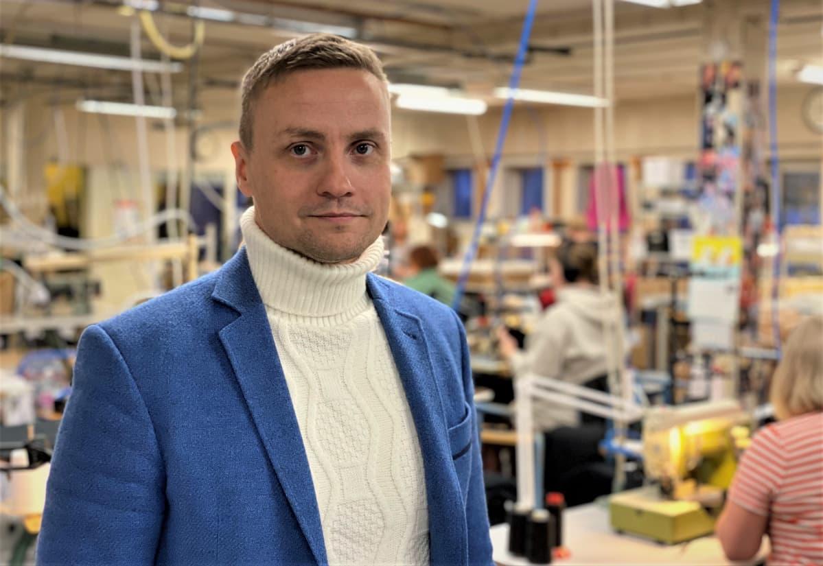 Toimitusjohtaja Tuomo Saarni sinisessä takissa ompelimossa.