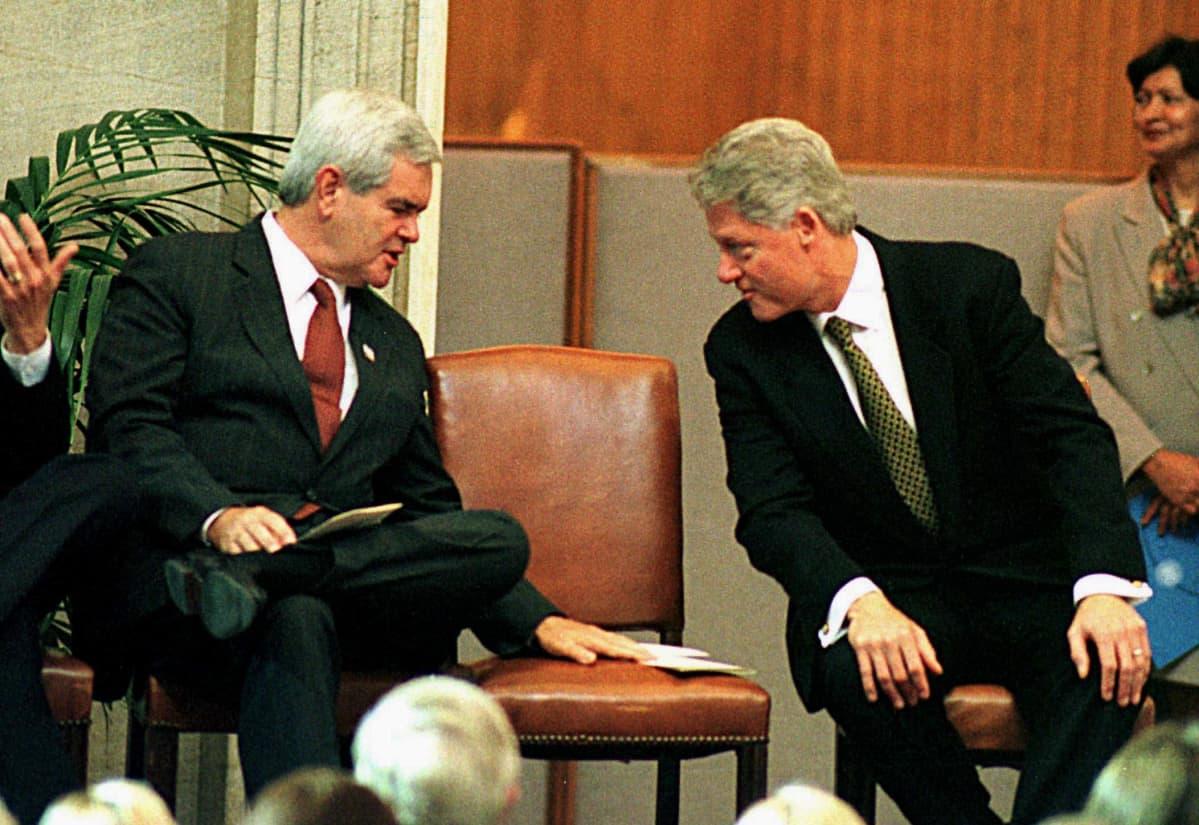 Newt Gingrich ja presidentti Bill Clinton istuvan vaivaantuneen näköisinä, välissä tyhjä tuoli.