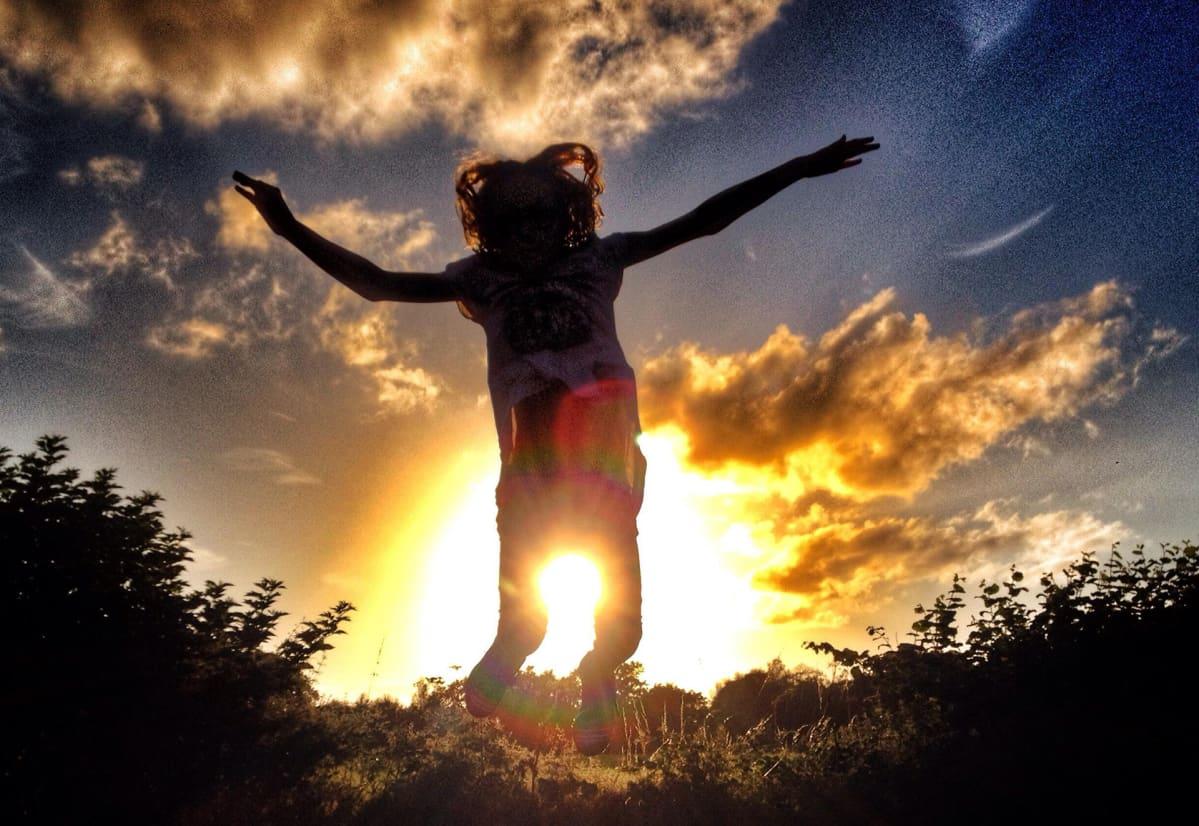 Nainen hyppää ilmaan aurinko takanaan.