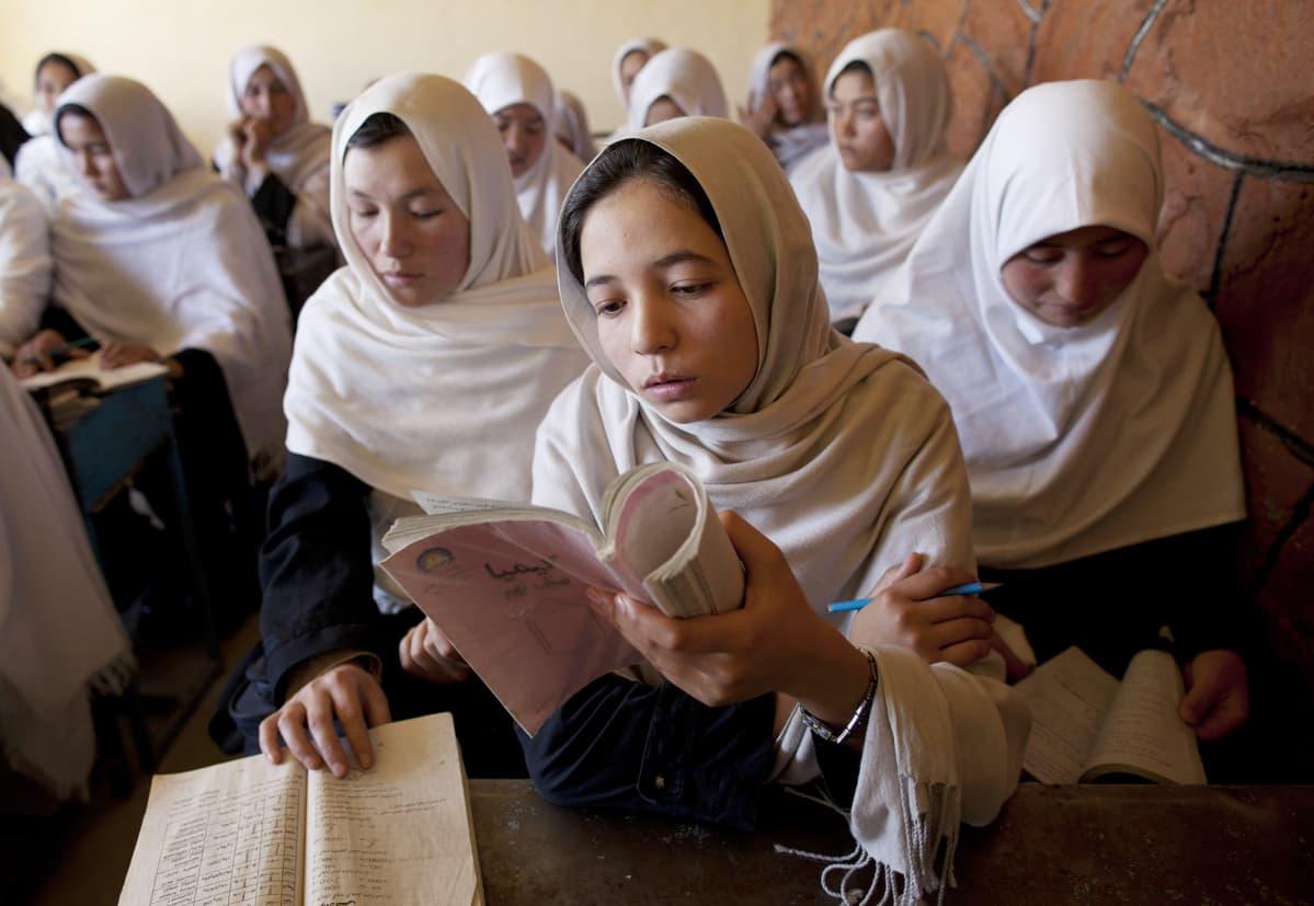 Afghanistanilaiset tytöt lukevat kirjaa koulussa.