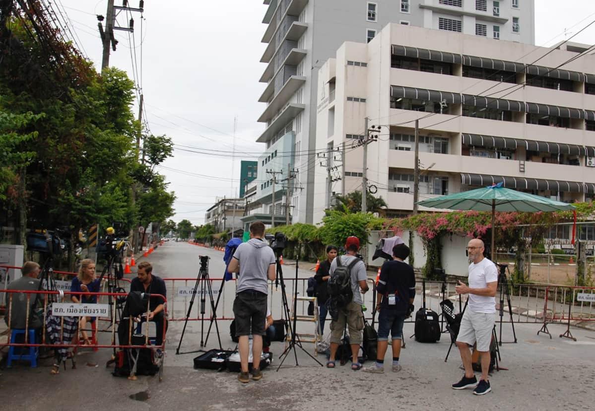 Joukko kuvaajia ja toimittajia on metalliaidan luona kameroiden kanssa. Taustalla näkyy harmaa kerrostalo.