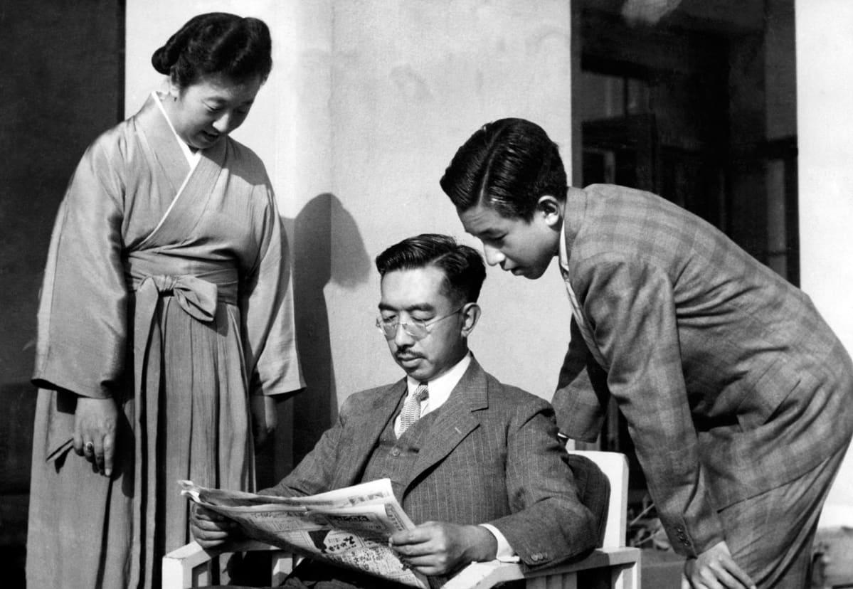 Japanin keisari Hirohito lukee sanomalehteä keisarinna Nagakon (vas.) ja poikansa Akihiton (oik.) kanssa Tokion keisarillisessa palatsissa 1950-luvulla.