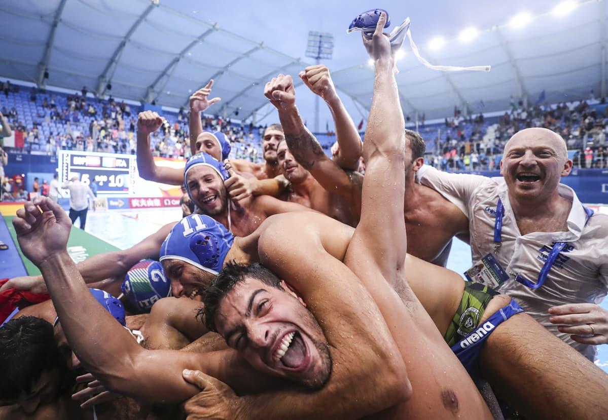 Italian vesipallojoukkue juhlii kultamitaliaan halaamalla ja hyppimällä toisetensa päälle.